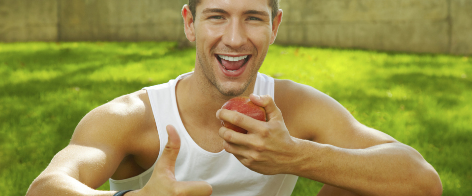 sport  man showing the sign ok and eating an apple